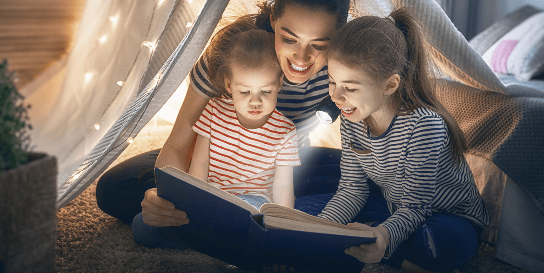 Family smiling and reading book